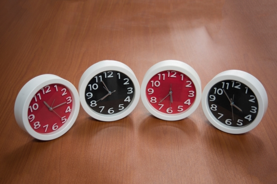 2 black, and 2 red clocks on a brown table, all with different time.
